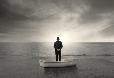 A man standing in a row boat, staring at the sea